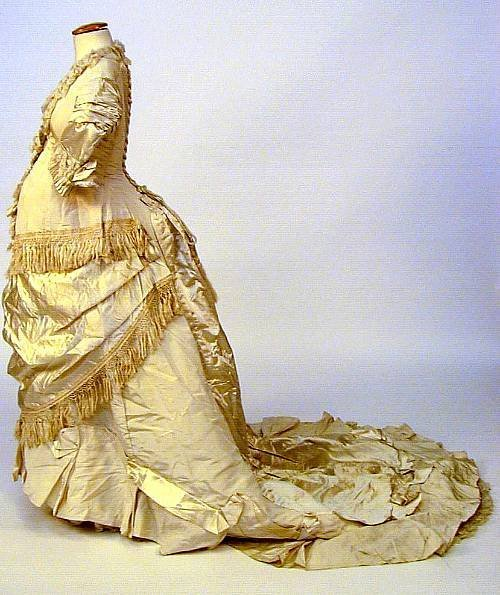 tinywaitress:  A one-piece maternity trained wedding gown, circa 1880, of cream finely  ribbed silk and ivory satin, with silk fringe and cord detailing, lace  trimmings to collar and cuffs, together with a white cotton trained  petticoat with bobbin lace detailing and a cream taffeta cape with  embroidered detailing.
