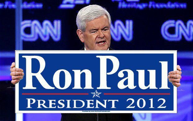 Newt Gingrich holding a Ron Paul for president 2012 sign.