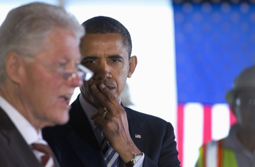 nationaljournal:  PHOTO OF THE DAY: President Obama listens as former President Bill Clinton speaks at a building under construction in Washington on Friday. (PHOTO: Carolyn Kaster/AP)