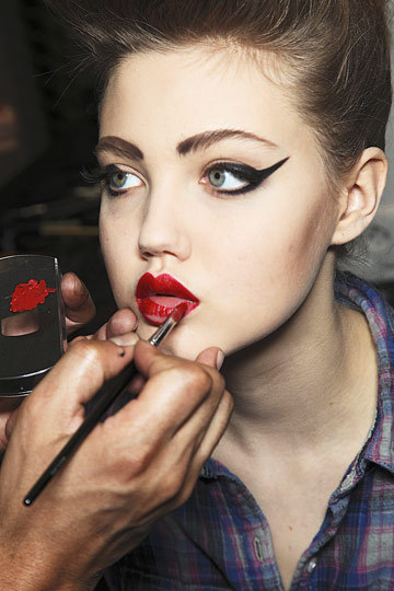 Lindsey Wixson in hair and makeup getting three of my favorite makeup looks in one: the cat eye drama, bold brows, and a red pout.