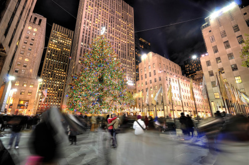 """Manhattan's Christmas Family Room"" by Brian Hoffsis At Rockefeller, during the month of December, everyone has something  in common – Christmas. Swarming with curious Midwesterners, wide-eyed  Europeans with surgically implanted smiles, Asians incapable of  detaching cameras from eye-sockets, local New Yorkers milling about with  that certain air of pride as if the entire city block were an extension  of their own living room, Rockefeller plaza, the home of NBC (love it  or hate it) and masterpiece Deco architecture really is the heart of the  city. In New York where home is rarely more than a 600 square foot room  with a tub in the kitchen the Rockefeller Christmas tree and  festivities are truly something to be proud of and for millions of New  Yorkers to claim as their own. I don't know which group this intimate couple finds themselves but  capturing their tender moment was an unexpected surprise to me. An open  shutter even in the busiest of intersections can reveal the warmest of  human affection."