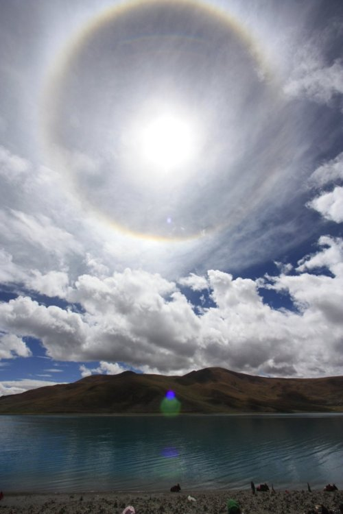 Tibetan Halo The particularly colorful halo featured above was snapped at Yamdrok Tso Lake, Tibet. This is a 22-degree halo — the radius of the inner ring to the Sun. by Alan Millar