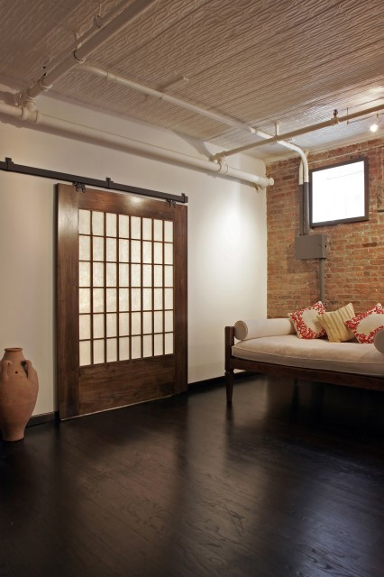 This stylish loft space features an exposed brick wall and a sliding barn door that is inset with frosted glass panels for a trendy modern look. (via Z-loft - modern - living room - new york - by Rodriguez Studio Architecture PC)