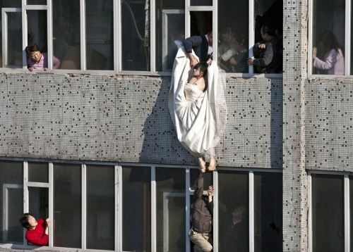 A distressed bride attempts suicide in China after her fiance abruptly  called off their marriage. Still in her wedding gown, she tried to kill  herself by jumping out of a window of a seventh floor building. Right as  she jumped, a man managed to catch and save her. 45 Most Powerful Images of 2011