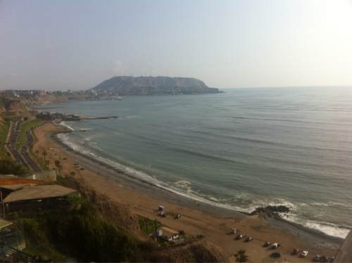 Coast of Lima, Perú from the Miraflores district. Football players, surfers, and paragliders enjoying the summer weather.