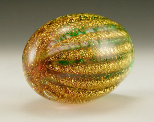 "Beautiful Italian Venetian gold ribbed watermelon paperweight.  Richly laden with spiraling ribs of gold flake and mimicking wisps of green and pink verde behind the gold.  Encased in crystal.  Looks like a mellon.  Intricate and beautiful. Click here to read more about Italian glass. The KB Italian Glass sticker tells us that this big beauty was imported from Italy during the 1960s to 1970s.  The 'Koscherak Brothers', established in 1887, brought huge amounts of Italian art glass to New York for distribution in the United States.  Although the export glass art was never signed by the original artists or glass houses, many were designed by well-known mid-century Italian Masters such as Fratelli Toso and Barbini.  The 'KB' sticker has been found coupled with A.VE.M. s(Arte Vetraria Muranese) sticker, a well-known Italian luxury glass maker. Made by hand. Weighs 2 lbs.  Stands 3½"" tall and 3"" wide."