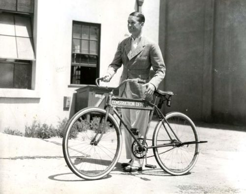 Maurice Chevalier walks a bike. And smokes a cigarette.