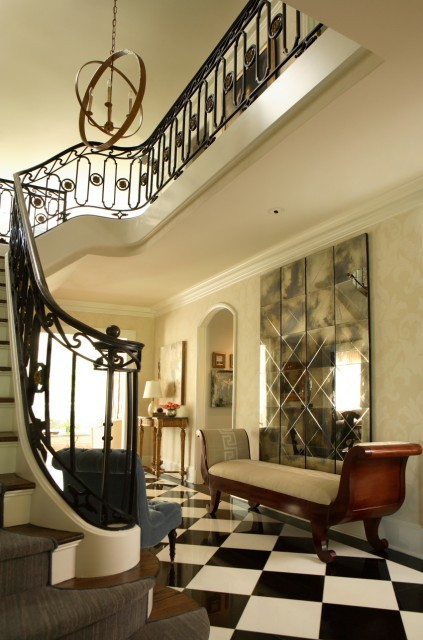 Strong architectural features, black and white marble floors, an antiqued gold iron light fixture, and an interesting and unusual staircase make for an arresting presentation in this entryway. (via 2010 ASO Showhouse - contemporary - entry - atlanta - by Dillard Design Group, LLC)