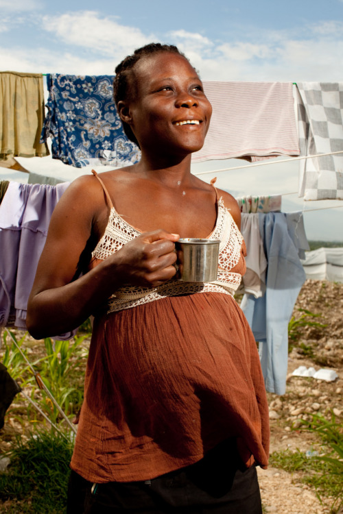 Vivian Cola, living in a tent camp in Port au Prince, drinks coffee prepared on her charcoal efficient stove. She also sells the coffee to her community, earning her an income. The stove  not only allows her to have her own business, but also drastically reduces smoke emissions, keeping Vivian's children and unborn baby healthier. Learn more at www.theadventureproject.org.