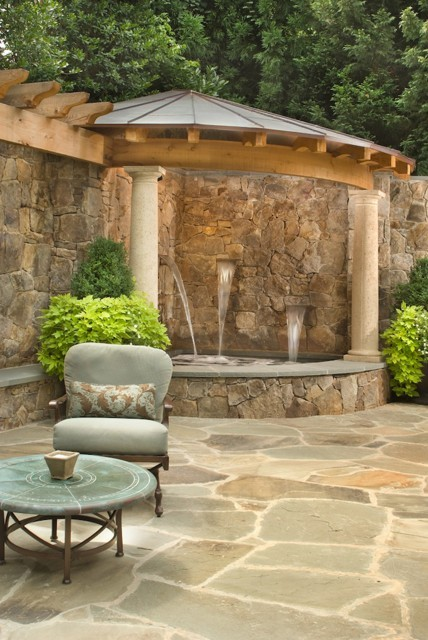 A discreet corner hot tub/spa, fed by cascading fountains, is surrounded by rock walls and covered with a roofed pergola in this beautiful backyard oasis (via Kohlenberger - traditional - landscape - dc metro - by Lewis Aquatech)