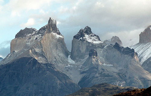scinerds:   Los Cuernos from Lago Pehoe (by twiga269 ॐ FreeTIBET)  Torres del Paine National Park (Parque Nacional Torres del Paine) is a national park encompassing mountains, a glacier, a lake, and river-rich areas in southern Chilean Patagonia. The Cordillera del Paine is the centerpiece of the park. It lies in a transition area between the Magellanic subpolar forests and the Patagonian Steppes. The park is located 112 km (70 mi) north of Puerto Natales and 312 km (194 mi) north of Punta Arenas. Bernardo O'Higgins National Park is its neighbour to the west, while Los Glaciares National Park is located to the north in Argentine territory. Much of the geology of the Paine Massif area consists of Cretaceous sedimentary rocks that have been intruded by a Miocene-aged laccolith. Orogenic and erosional processes have shaped the present-day topography, glacial erosion being the main one responsible for the sculpturing of the massif in the last tens of thousands of years. A good example of the latter are the Cuernos del Paine, whose central bands of exposed granite strongly contrast with the dark aspect of their tops, which are remnants of a heavily eroded sedimentary stratum. In the case of Las Torres, what once was their overlying sedimentary rock layer has been completely eroded away, leaving behind the more resistant granite.