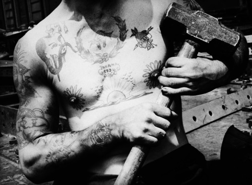 Torso of tattooed shipbuilder Leonard Long holding a sledgehammer at Bethlehem Shipbuilding's drydock plant. 1937 Photo by Margaret Bourke-White