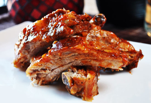 prettygirlfood:   Whiskey Glaze RibsIngredients & Directions: Rib Spice Rub:(yields ~8.5 tablespoons of seasoning, use as needed.)- 4 tablespoons kosher salt- 1 tablespoon coarse ground black pepper- 1 tablespoon dried onion- 1 1/2 teaspoons dehydrated garlic- 1 1/2 teaspoons crushed red pepper flakes- 1 1/2 teaspoons dried thyme- 1 1/2 teaspoons sweet or spicy paprika- 1 1/2 teaspoons dried mustard seed. Combine all ingredients, and crush with a mortar and pestle, or spice grinder. Season liberally, enough for four to six racks of ribs– adjust the recipe as needed, or save the rest in an airtight container for later.  Whiskey Glaze:(makes ~ 3 cups, enough for 2 large rib racks)- 1 cup whiskey (I used Canadian Club… cook with your whiskey of choice; Jack Daniel's works well too)- 1 cup ketchup- 1/2 cup dark brown sugar- 1/4 cup apple cider vinegar- 1 tablespoon lemon juice- 2 teaspoons low sodium soy sauce  (sub worcestershire sauce if preferred)- 3 cloves garlic, minced (adjust to taste…heck, I used 5)- 1 teaspoon yellow mustard- salt and pepper to taste Combine all of the ingredients in a sauce pan, and stir until incorporated. Simmer over medium-low heat for 20-30 minutes, stirring often,  taking caution not to burn the sauce. Store in an airtight container in the refrigerator. You can make this sauce a few days ahead of time, giving flavors time to develop. Always use this sauce toward the end of the cooking, so it doesn't burn. 1. Pre-heat oven to 375′F. Line a baking sheet with foil, and fill 1/2 way up with warm water. Slice half a lemon, and place them on the bottom of the pan– use the juice of the other half to season the water. 2. Carefully lay your seasoned ribs, concave (bone) side down, in the water-citrus bath. Carefully wrap the baking pan in tin foil, creating a tent to allow for steam to build up. Bake for 30-45 minutes.  3. Remove from the oven, and allow to cool for 5 minutes. Carefully open the foil tent– steam will escape, so take caution, and gently unwrap the foil from the baking sheet.  If there is water at the bottom of the baking sheet, carefully drain it out. Using a pastry brush, liberally glaze the ribs with the whiskey sauce on both sides. 4. Lower temperature to 325′F, return to the oven uncovered, and continue cooking for 8-10 minutes. Remove from the oven, and reglaze the ribs, returning them to the oven once again. I repeat this step 3 times, for a total of ~30 minutes, ensuring that the ribs are well glazed so they don't dry out. * If you are a barbeque master, you can finish the ribs on the grill instead of the oven. Allow to cool slightly before portioning off the ribs. Enjoy