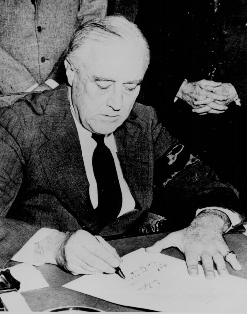 "President Franklin D. Roosevelt signing the Declaration of War against Japan, December 8, 1941. (National Archives) Listen: ""Yesterday, December 7, 1941— a date which will live in infamy…"" Crafting The 'Day In Infamy' Speech More: Pearl Harbor Survivors 