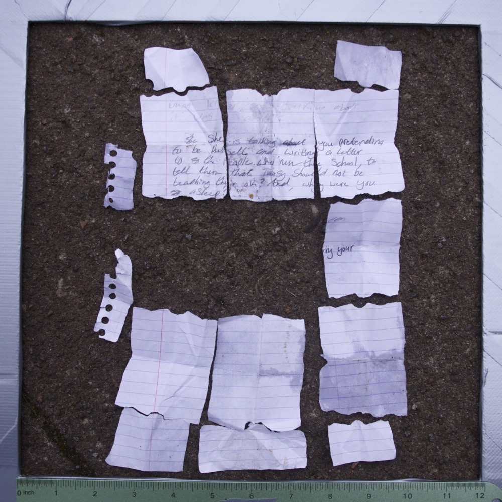 Torn up paper with two-part conversation on sidewalk, partially reconstructed, N Van Houten Ave. The text reads:  What letter is ????? talking about it was a ??? She She is talking about you pretending to be Russell and writing a letter to ?? the people who run the school, to tell them that Tansy should not be teaching their. ok?  And, why were you ?? asleep? ??????????? een ??????????? my your