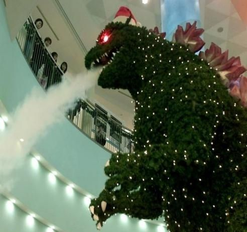 prostheticknowledge:  Godzilla Christmas Tree  Yes, a Christmas tree in the form of Godzilla …  Godzilla-shaped Christmas tree spews smoke, Aqua City Odaiba shopping mall, Tokyo, Japan. (2006)