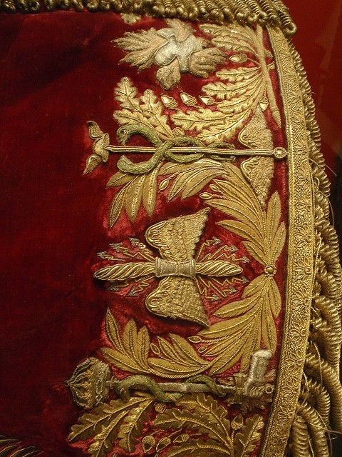Elegant gold embroidery on red velvet - part of French officer's uniform  Hand-embroidered, ca. 1800. The details are breathtaking. It's also amazing that this and so many other uniforms survived.   I am ridiculously interested in the caduceus but I can't find anything about why it would be on the uniform or what the other symbols stand for.