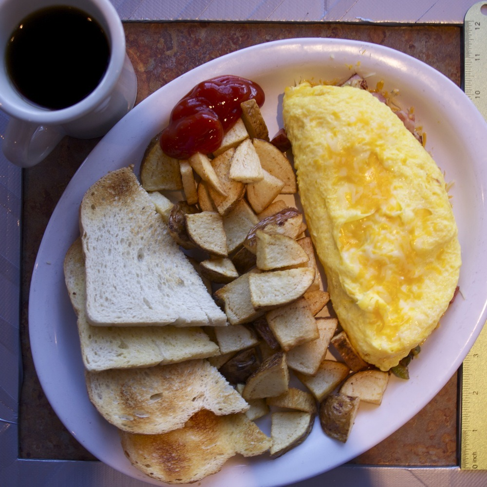 "Denver omelet, potato chunks, sourdough toast, coffee, Darcy's on N Lombard St. This place used to share space with University Coffee on the corner as sort of separate-but-connected restaurants but it seems like they've taken over the whole lot more recently. I actually have a Darcy's membership card that I think would eventually net me a free meal but I don't eat here very often and feel a little bit like an idiot for even bothering to bust it out just to save five bucks a year on breakfast.  Though the time I ate there after the time that I got the card, the waitress asked while running my check if I wanted to get a card and I said ""I've actually got one"" and she shouted ""THAT IS A GOOD LIFE DECISION, MAN"" and that was kind of great."