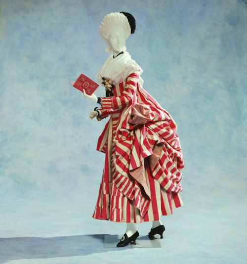 "Robe retroussée dans les poches, ca 1780 France, KCI  In accordance with the English custom of walks in the countryside and  relaxing in the open air, it became popular to dress up in clothes  derived from the work clothes and townwear of ordinary people, who, by  their nature, put great importance on freedom of movement. One of these  so inspired style is the ""retroussée dans les poches"", as seen here. The  gown's hem is pulled out from slits in either side, and draped on the  back. The red and white contrasting pekin stripes also heighten the  folds' effect. ""Pekin"" stripes are textiles originally made in China of equal-width  striped patterns of differing colors and weaving methods. Along with the  expansion of interest in chinoiserie, around 1760, Peking striped  fabric was even produced in France and became popular. As Jean-Baptiste  Siméon Chardin(1699–1779) painted (""The Morning Toilette"", c.1741,  Nationalmuseum, Stockholm) , women of the rich bourgeoisie often wore  this kind of striped pattern.  I don't care how many times I post this."