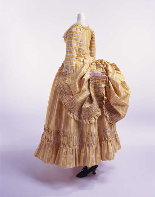 "Robe à la polonaise, ca 1780 France, KCI Fashionable men and women of the late rococo era loved all things rustic.  Their version of rustic, anyway.  A popular form of portraiture in this era was the pastoral portrait, where the female sitter was dressed as a ""shepherdess"" who looked like she had never worked a day in her life.  Likewise, the polonaise was an idealized imitation of ""rustic"" country dress.  Working women would tuck their skirt up through their pockets to keep it out of the mud."