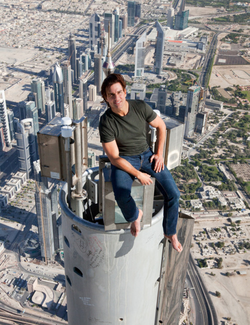 Tom Cruise on The Burj Khalifa This deserves a post. Tom Cruise (yeah, he's nuts, I know!) sits on top of the Buj Khalifa.  What's crazy about this is that he wore no harnesses. I thought it was actually fake till I saw this snapshot below of him doing it.  If you want to see how high this is, considering it's the tallest building in the world, take a look at this video:   Yeah, how about never.