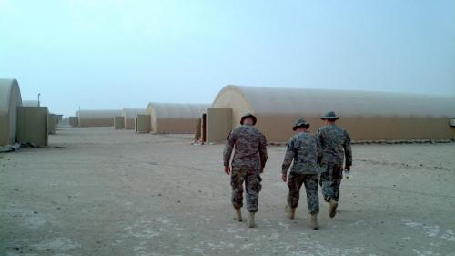 3 soldiers walk around in the desert area towards their tents after a long day. Courtesy of Michael Eller