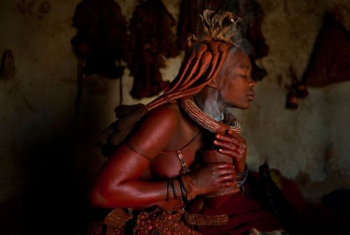 The Himba Women of northern Namibia perform daily rituals where they anoint themselves with a mixture of ochre, oil and ash to protect themselves from the harsh desert climate and rather burn aromatic herbs in a pot each morning with which they smoke themselves as if applying perfume. (Photo and caption by Dominique Brand / 2011 National Geographic Photo Contest)