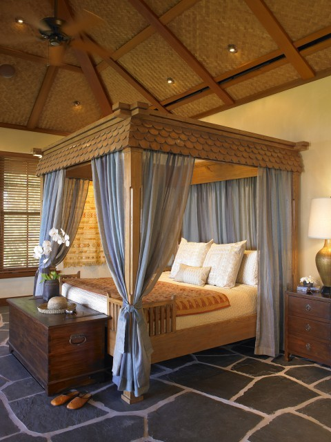 A beautiful bedroom in a Hawaiian home features a carved four-poster bed with draperies, and a black stone floor (via Dara Rosenfeld Design)