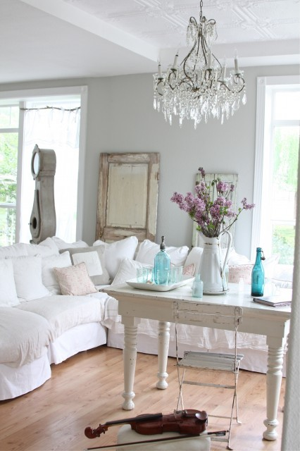 A brilliant white living room shows a shabby chic influence with a slipcovered sectional sofa strewn with plump cushions, a distressed painted farmhouse table, and glittering crystal chandelier. (via Dreamy Whites)
