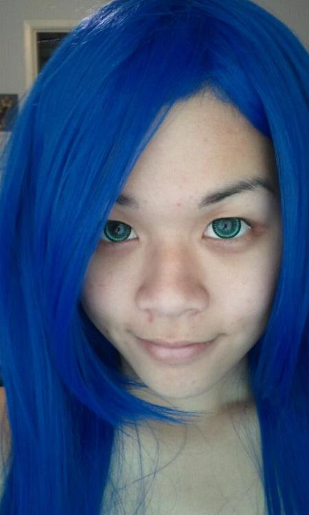Progress picture for Konata of Lucky Star. Crooked cat smile! :3 Contacts and wig (same wig as Wendy). Just need to cut bangs and style.