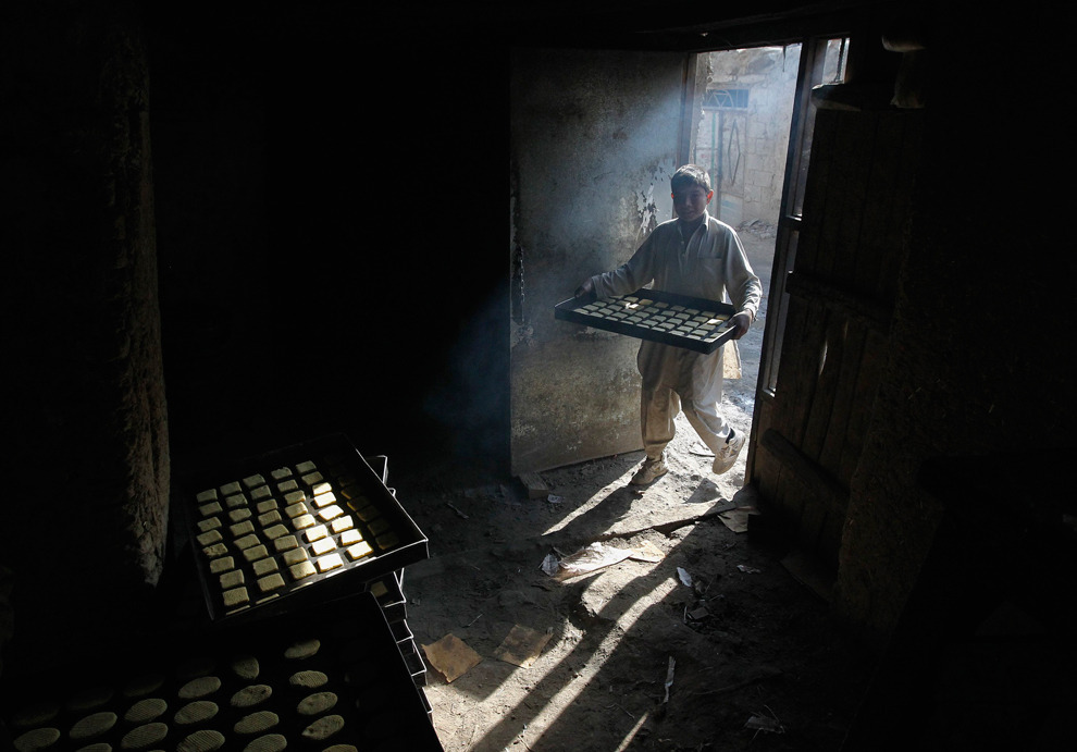 An Afghan boy carries a pan of sweets at a small confectionery factory in Kabul, Nov. 20, 2011.