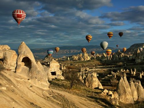 nationalgeographicdaily:  Hot Air Balloons, CappadociaPhoto: Kani Polat The success of a photograph almost always comes from planning, and luck definitely favors the prepared. In this shot of hot air balloons over ancient rock formations in Turkey, the photographer no doubt planned ahead to make sure he was in the right place at the right time. First, the cone-shaped rock formations complement the similarly shaped balloons. I especially love that one larger formation is included on the left. Not only is it a bold shape to have close to the camera, but it also has a curious, cave-like element and speaks to the geological history of the setting, giving the image that all-important sense of place. Second, the early-morning light raking in from the right is perfectly lovely, as are the soft clouds, which were a lucky element. Finally, the balloons are beautifully placed across the sky, but the red balloon in the upper left of the frame is the final, key element to the success of the image.