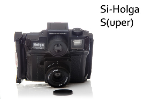 The new Si-Holga S(uper).  Features :  -TLR Finder (that flips into a sports finder when you don't want to look down) -On camera flash with colored gels  -Shoot polaroid Type 100 film! (Images are 6x6cm squares)