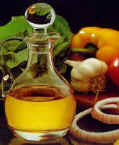 "FEATURED INGREDIENT :  OLIVE OIL Some say that the best olive oils come from the Mediterranean,  but whilst countries such as France, Greece, Italy,  and Spain all produce fine specimens, olive oil is also produced in many other countries such as Argentina, Australia, Egypt,  Israel,  Lebanon,  South Africa,  Tunisia, Turkey and New Zealand, with the largest producers worldwide being Spain, Italy, Greece, Portugal, Tunisia, Turkey, Syria. Origin and History of Olive Oil Olive oil is one of the oldest culinary oils. The olive tree is native to Asia Minor and was first thought to be cultivated in Syria about 6,000 years ago. It spread to the rest of the Mediterranean around 5,000 years ago and was being grown in Crete by 3,000 BC.  Both scriptural and classical writings refer to both the oil and the tree as  as a symbols of goodness, purity, peace and happiness. According to legend,  the first olive tree grew on Adam's tomb and don't forget olive branch brought to Noah on the ark  signaling the end of the flood.  In addition to its  culinary use,  the oil was burnt in the sacred lamps of temples, while the victor in the Olympic games was crowned with its leaves and by the time they were established in Egypt, they were so highly prized that  the great Tutankhamen had olive branches placed in his tomb.  The use of olive oil spread rapidly around the Mediterranean and across the ancient world and has been a foundation of the Mediterranean diet for thousands of years. Cultivation and Processing of Olive Oil  Before we can talk fully about olive oil, mention must be made of the tree which produces the fruit from which it is extracted. Olive trees have a life span of 300 to 400 years and grow to a height of 6m/20 feet or more. Depending on the variety,  they produce fruit varying from green to black however, olive oil is only made from green olives and just as with wine, the flavour, colour, and consistency vary due to different olive types, location, and weather.  In order to achieve the finest quality olive oil, the fruit must be harvested at its optimum stage of ripeness and pressed within 72 hours. The best harvesting method is hand picking, but this is labour intensive which is reflected in the price. The reason for this is to prevent the fruit being bruised in the picking process which causes tartness and higher acidity.  Once picked, the traditional method of obtaining olive oil starts with the  crushing the washed and stemmed olives with huge stone wheels, however this has been surpassed by  commercial hydraulic machinery in many instances.  Whether traditional or modern, the process remains the same. Once crushed the paste is pressed, ensuring heat isn't allowed to build up as this affects the flavour (cold pressing),  then the resulting liquid is separated into water and oil, nowadays often using a centrifugal separator.  The resulting oil from this first pressing is the best quality and designated the name ""Extra Virgin"". That's the basics, but olive oil grading is much more complicated so  below are listed some of the types of oil with a brief explanation of  the standards that have to be achieved for each type. Grades of Olive Oil Olive oil is graded according to its flavor, colour, and aroma, as well as its acidity. As mentioned above, many factors contribute to the overall quality, but below are the basic requirements for each type. Premium Select (fine) Extra-Virgin Olive Oil  This is the crème de la crème of olive oils.  It has a rate of acidity which is less than 1% with some as low as .225%. This level of quality is achieved through hand harvesting and cold pressing within 24 hours, thus ensuring the highest degree in both quality and taste.  Extra-Virgin Olive Oil Any olive oil that is less than 1% acidity, produced by the first pressing of the olive fruit through the cold pressing process can be classed as an extra virgin oil but a word of warning - many extra virgin olive oils are extra virgin in name only, meeting only the minimum requirements. 'Extra virgin' is a chemical requirement that does not necessarily indicate quality or taste. In general, the deeper the colour, the more intense the olive oil flavor.  Virgin Olive Oil This is made from olives which are slightly riper than those used for extra-virgin oil. Whilst it is still unrefined, it has a slightly higher level of acidity (1-1/2 to 2%) and is generally milder than extra virgin olive oil.  Pure Olive Oil This is solvent-extracted from the olive pulp, skins, and pits then refined (also called commercial grade oil).   It is lighter in colour and blander than virgin olive oil. The word ""pure"" refers to the fact that no non-olive oils are added. Other than that, its mediocrity is such that it's really not a worthy competitor for cupboard space. Buying and Storing Olive Oil When buying olive oil in bulk,  transfer into smaller containers, preferably to a  dark-coloured  bottle as air, heat, and light will cause olive oil to turn rancid. Always store in a coolish, dark place and be sure containers are  tightly sealed.  Avoid  plastic containers as the oil can absorb PVCs.  In very cold conditions, olive  oil may turn cloudy and even solidify, but it will clear again as it warms up, so cloudiness should not be taken as an indication that the oil isn't still usable. Olive oil can be refrigerated but doing so will cause it to congeal and turn cloudy although it should not affect flavor.  Olive Oil and Health Due to its fatty acid composition, olive oil has a beneficial impact on controlling cholesterol levels and thus has a unique part to play in the prevention of cardiovascular disease. It is also believed that antioxidant substances such as vitamins E, K and polyphenols which are found in olive oil, delay aging and prevent carcinogenesis, liver disorders and inflammations.  It is very well tolerated by the stomach and is believed to lower the incidence of gallstone formation as well as promoting bone mineralisation, and is therefore excellent for those who have bone calcification problems.  All in all, a superb ingredient as far as health benefits are concerned. Olive Oil in Cooking Cooking with olive oil is like cooking with wine: never use an olive oil that does not taste or smell at its best.  Since olive oil is not distressed during extraction,  it's very stable, especially for frying. Contrary to common belief, deterioration when frying is much lower in olive oil than in other oils. Try adding a little olive oil to the pan when a recipe calls for frying in butter. A higher temperature can be achieved with less fear of the butter burning. Also like wine, different flavours of olive oil are best suited to different uses. As a general guide, use a milder olive oil with grilled fish,  raw, cooked or steamed vegetables, soups and pasta sauces and use the fruity, stronger olive oils with grilled meats, pastas, cooked vegetables, cheeses and Bruschetta. But most of all EXPERIMENT. Olive oil can also be used very successfully in baking, replacing or reducing the need to use butter or margarine. Recipe with Olive Oil:  Salmon Carpaccio Ingredients: 1tbsp lemon juice 5 tbsp Extra Virgin Olive Oil 1 sprig Aniseed  Salt 300g/10oz Fresh Salmon, very thinly sliced (wafer thin) 2 Spring Onions, finely sliced  1 Tomato, finely diced 25g/1oz Capers Black Pepper French Bread to serve Instructions 1. In a small mixing bowl, mix together the lemon juice, oil,  salt and aniseed to make a sauce.  2. Place the salmon on a shallow serving dish then sprinkle the onions,  diced tomato and the capers evenly over the top. 3.  Drizzle the sauce over the top and season with black pepper. Serve immediately with French bread. Serves 4"