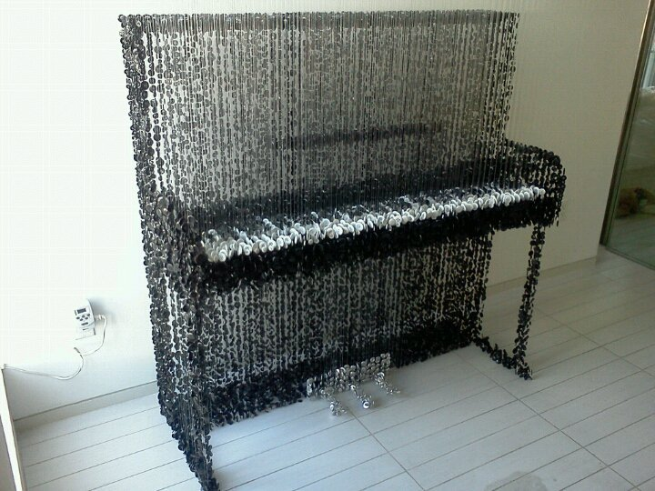 Upright Piano (2011) by Augusto Esquivel. 45 lbs of black and white sewing buttons, monofilament, and acrylic.