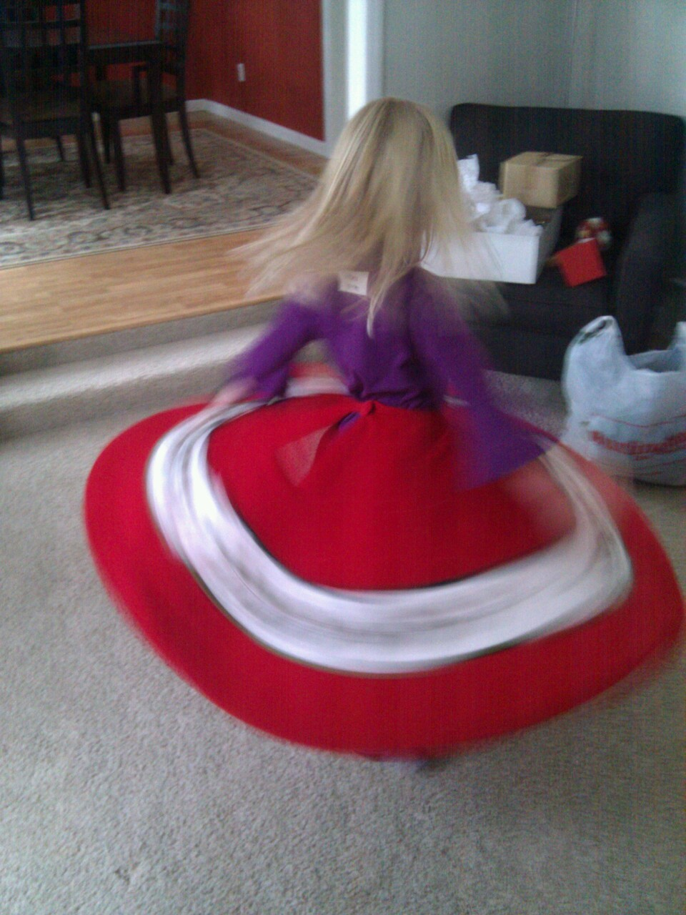 My little whirling dervish wearing the tree skirt.