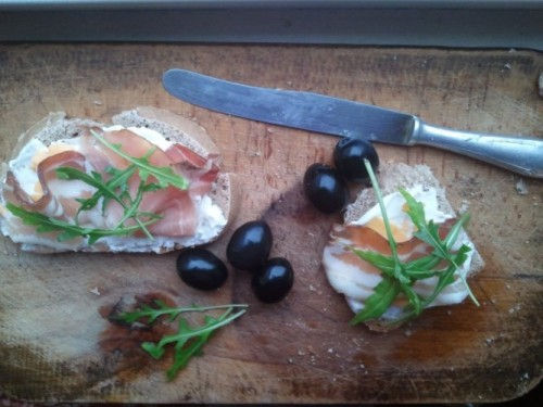 Bacon + Prosciutto = my Lunch Basis: homemade bread Spread on it: bio sauer cream Proteins: bacon and prosciutto On top: rucola On the side: black unsalted olives Picture taken with Samsung Galaxy S
