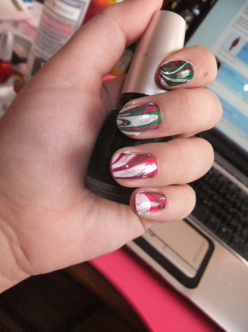 Christmas water marbling! This is my first ever attempt at water marbling, and overall I'm pretty happy! If I did this exact thing again I might use a different red, as this turned out a little pink for my tastes, especially on the thumbs or the nails where there's a lot of red visible. Also, it looks like I messed up my pattern on my left ring and pinky, and started with red instead of green but whatever. Still pretty snazzy! Base: Sally Hanson X-Treme Wear in White On For marbling: China Glaze in Phat Santa and Jolly Holly, Sally Hansen X-Treme Wear in Celeb City