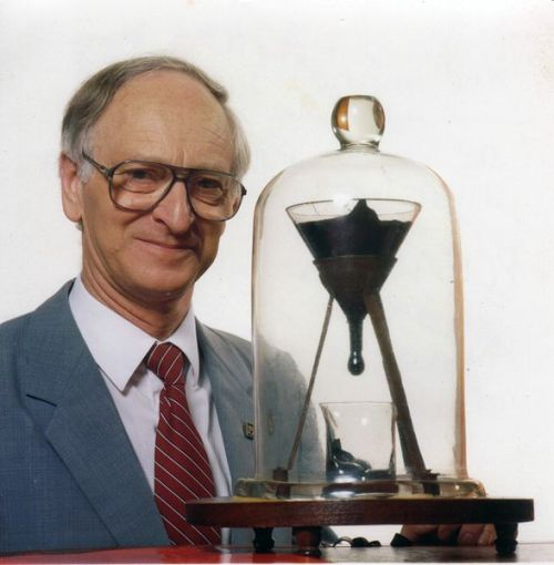 The pitch drop experiment is a long-term experiment which measures the flow of a piece of pitch over many years. Pitch is the name for any of a number of highly viscous liquids which appear solid, most commonly bitumen. At room temperature, tar pitch flows at a very slow rate, taking several years to form a single drop.  The most famous version of the experiment was started in 1927 by Professor Thomas Parnell of the University of Queensland in Brisbane, Australia, to demonstrate to students that some substances that appear to be solid are in fact very-high-viscosity fluids. Parnell poured a heated sample of pitch into a sealed funnel and allowed it to settle for three years. In 1930, the seal at the neck of the funnel was cut, allowing the pitch to start flowing. Large droplets form and fall over the period of about a decade. The eighth drop fell on 28 November 2000, allowing experimenters to calculate that the pitch has a viscosity approximately 230 billion times that of water.  This is recorded in the Guinness Book of Records as the world's longest continuously running laboratory experiment, and it is expected that there is enough pitch in the funnel to allow it to continue for at least another hundred years. To date, no one has ever actually witnessed a drop fall.  The image above features The University of Queensland pitch drop experiment with its current custodian, Professor John Mainstone (taken in 1990, two years into the eighth drop). Credit: John Mainstone and The University of Queensland