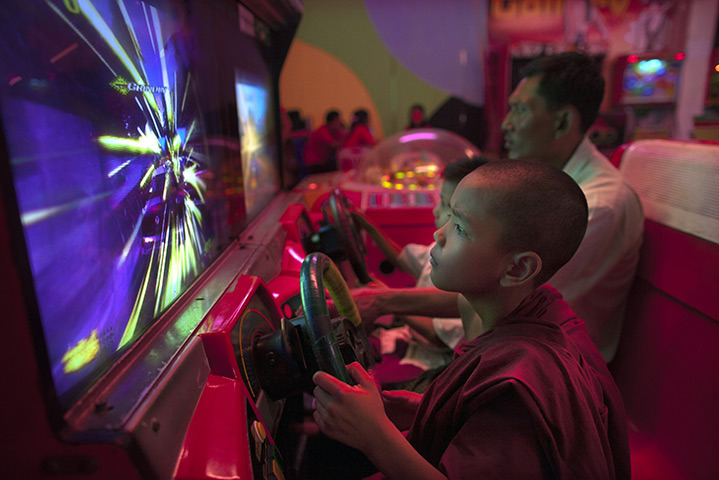 Rangoon, Burma. A novice monk plays a video game at Happy World amusement park. [Credit : Paula Bronstein/Getty Images]