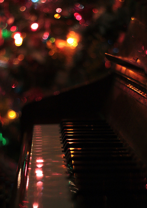 christmas tree lighting while sitting next to the piano.
