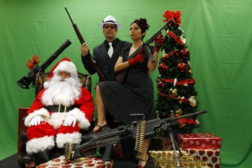 Todd Engle (center) and Mary Rose Engle (right) hold weapons as they  pose for a Santa photo at the Scottsdale Gun Club in Arizona. Is it just us, or does Santa look like a conscientious objector in this picture? See more delightfully festive Santa photos from around the world.(Photo: Reuters/Joshua Lott)