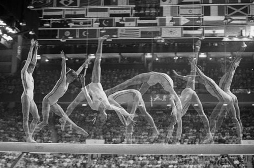 theraconteurasaurus:  Multiple exposure shot of Nadia Comaneci's routine on the balance beam at the 1976 Montreal Olympic Games. Her 18 July 1976 performance on the uneven bars was the first-ever perfect score of 10.0 in the history of the Olympics. Except, the Swiss Timing scoreboard wasn't built to record a 10, so her perfect score was instead displayed as 1.00.