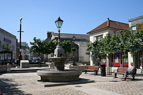This is the town square of Camborne, a town situated in western Cornwall, part of a conurbation, alongside the village of Pool and the town of Redruth. With a lovely Cornish name meaning 'crooked hill', Camborne was originally a small hamlet called Camborne Churchtown until the copper and tin mining boom in the late 1700s, when it was transformed into one of the many prosperous centres of the Cornish mining industry. It was home to the renowned Dolcoath Mine, which was once the world's deepest mine, with its principal shaft delving to an astounding 3,500 feet underground. Annually, the residents of Camborne celebrate Trevithick Day in honour of engineer Richard Trevithick, who in 1801 launched on Camborne Hill the world's first self-propelled passenger vehicle  - a steam-powered road locomotive nicknamed the Puffing Devil. As part of Trevithick Day, a parade of steam engines puff their way through town, and - an essential part of any good festival - there's a lot of dancing to join in with.