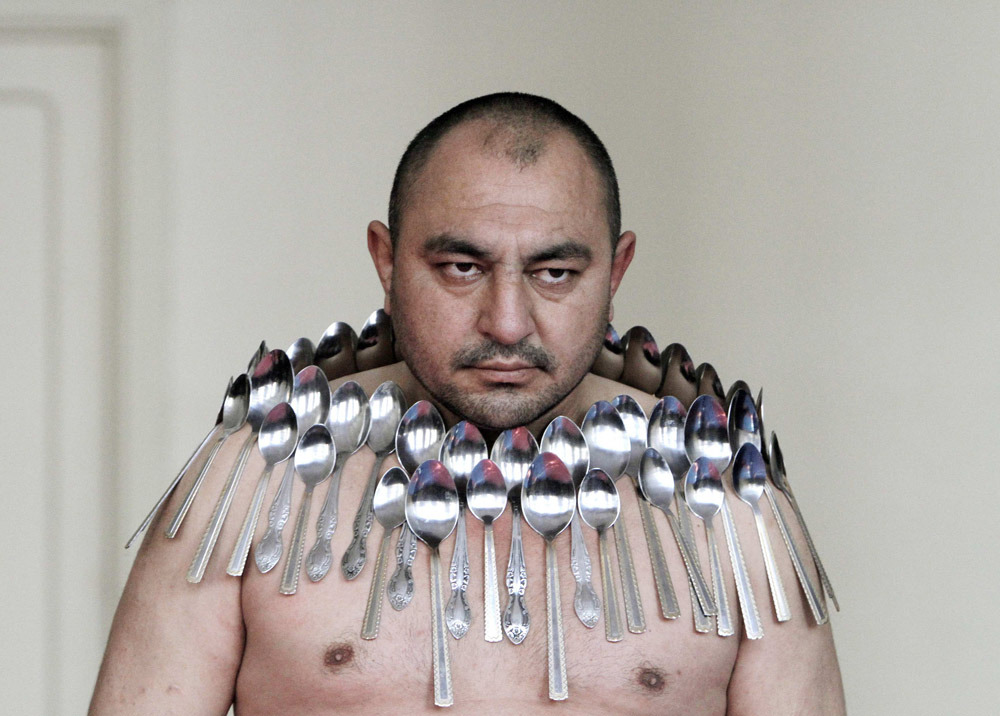 "Photos of the dayEtibar Elchiyev poses with 50 metal spoons magnetized to his body during an attempt to break the Guinness World Record for ""Most spoons on a human body"" in Tbilisi, Georgia, Dec. 14, 2011. (Photo: David Mdzinarishvili/Reuters)"