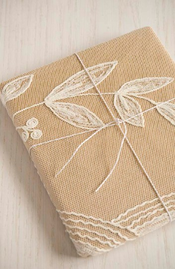 Wrap your gift in craft paper, then cut a piece of lace to fit around the box, and fasten on with hot glue gun. Easy peasy!