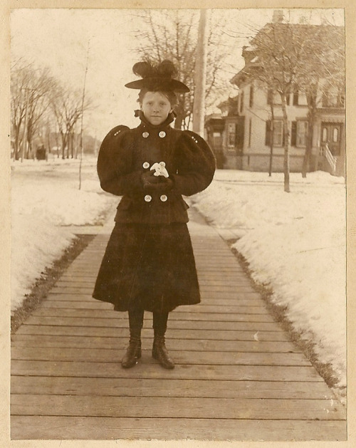 A girl wearing a very fashionable winter ensemble circa 1895. I love the button detail on the sleeves. Also note the amazing wooden sidewalk. My scanner's not high quality enough to show it clearly, but her cheeks and nose are absolutely covered in freckles. I adore this picture more than I can possibly say. (From my personal collection.)