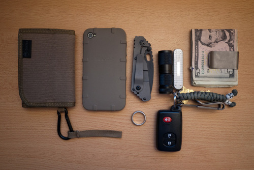 submitted by georgechen  - Hazard 4 mil-wafer wallet. - iPhone 4 + Magpul case.- Strider PT in black.- Car key.- 4Sevens Qmini.- Swiss Army knife USB drive 4GB + tiny scissor version.- Mega Dangler.- Short 550 Paracord.- Titanium Money Clip.  Editor's Note: Good example of a minimalist carry here. You have a super-solid primary EDC blade that isn't excessively long or unwieldy for most EDC tasks, backed by a keychain system providing your illumination and multitool functions. The keychain is kept slimmed down but also offers added utility in both the paracord lanyard for cordage and retrieval, and the Munroe Megadangler works as both a bottle opener type tool and a suspension clip to carry your keys easily in pocket. Lastly, separating your cash and cards into a wallet and moneyclip can better distribute bulk for a more symmetrical carry, which can free up space in some pockets and utilize some unused pocket space in others for a more balanced, comfortable feel. Good work, thanks for sharing!