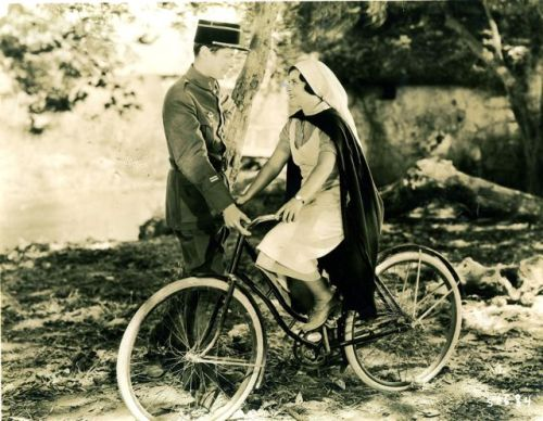 June Walker rides a bike. Robert Montgomery gets a grip.