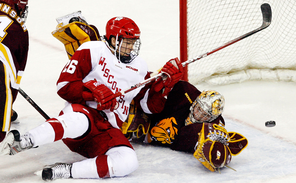 Wisconsin's Brad Navin and Minnesota-Duluth's Kenny Reiter watch the puck sail right of the goal in an NCAA college hockey game in Madison, Wis. on December 9, 2011. (Photo by M.P. King) (via Boston.com)